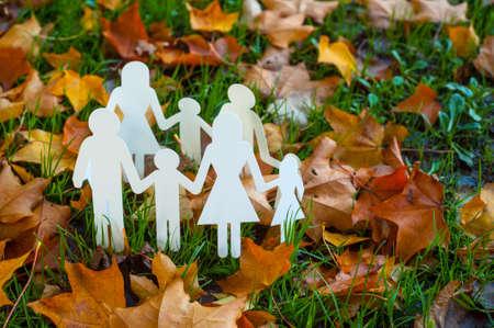 Paper family cut outs on autumn leaves Banco de Imagens