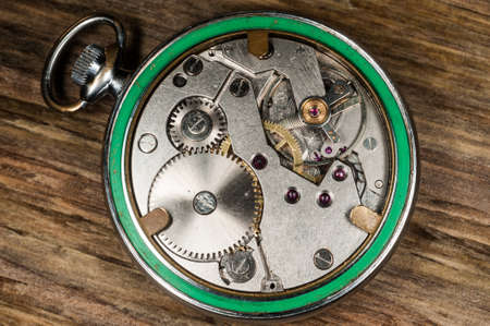 pocket watch mechanism wood background  photo