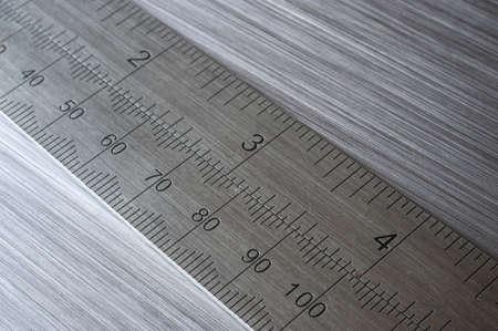 millimetre: metal ruler on brushed metal background