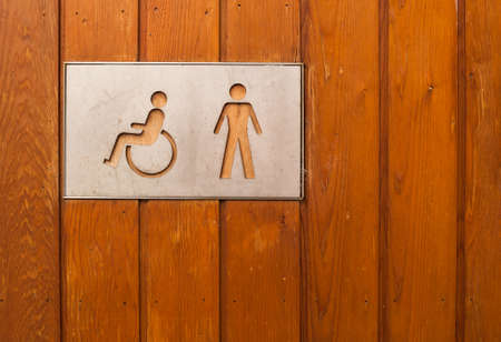 loo: handicap and men toilet sign on wooden background