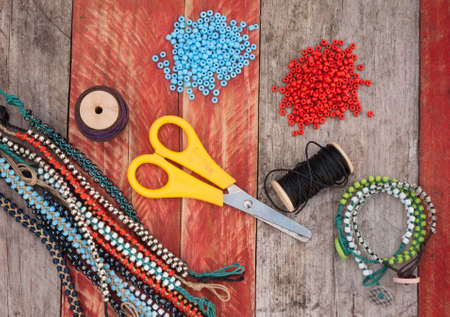seed beads: bead making accessories on grunge wood background Stock Photo