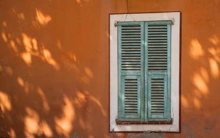 green french window shutters on orange wall tree shadows Reklamní fotografie