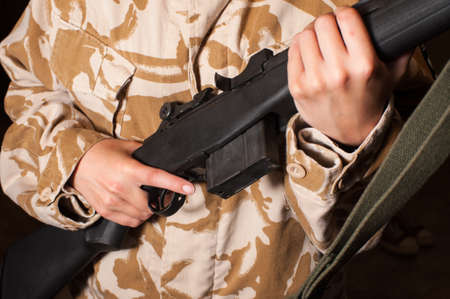 camoflauge: close up of person holding rifle