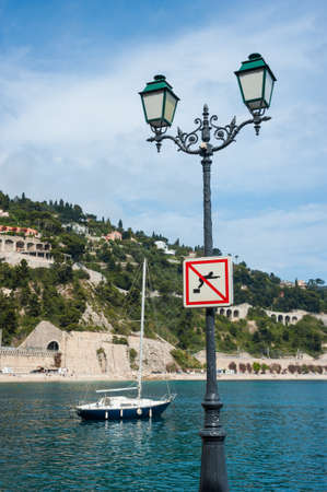 villefranche sur mer: sailboat and street lamp of villefranche sur mer in the south of France