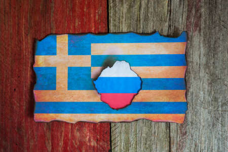 complications: russian flag behind burnt Greek flag background Stock Photo