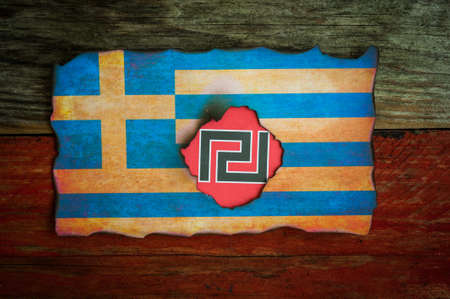 fascist: Greek fascist symbol behind grunge burnt greek flag background Stock Photo