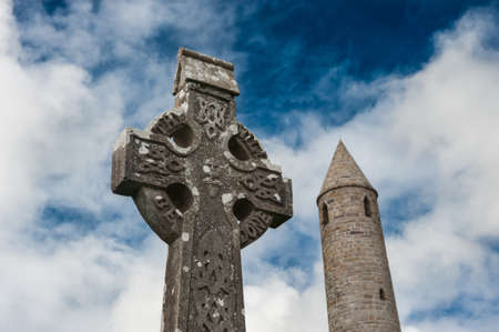 irish history: Celtic gravestone in front of Rattoo round tower in north Kerry,Ireland Stock Photo