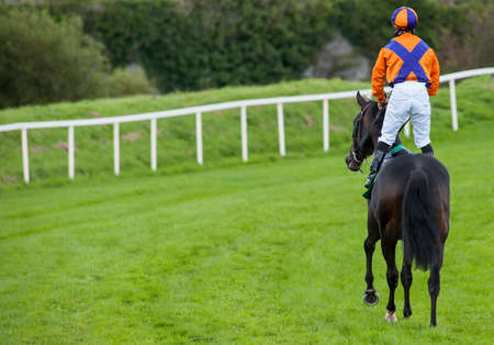 jockey standing up on race horse riding down the track