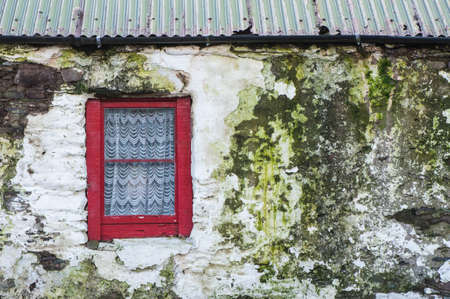 irish history: detail of red window on old weathered farmhouse in north county Kerry, Ireland
