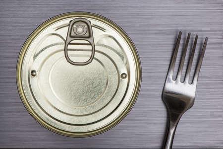 brushed metal background: shiny aluminium food can and fork on brushed metal background Stock Photo
