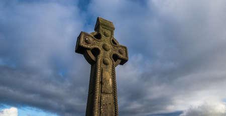irish history: celtic cross gravestone with dramatic stormy sky background