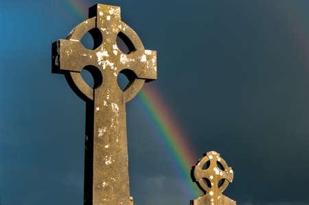 ancient ireland celtic cross: Rainbow over Irish celtic cemetery Stock Photo