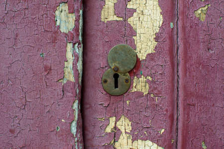 old wooden door: Vintage copper keyhole on grungy door of old abandoned building