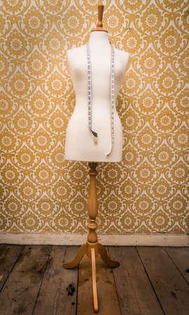 female form: mannequin dress form and tape measure vintage background