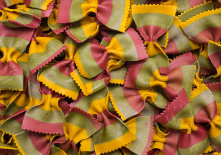 unboiled: tricolor Farfalle pasta background Stock Photo