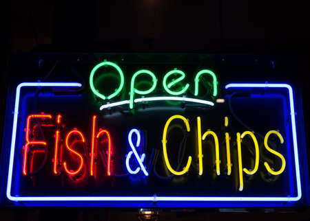 neon fish: Fish and Chips restaurant neon sign background Stock Photo
