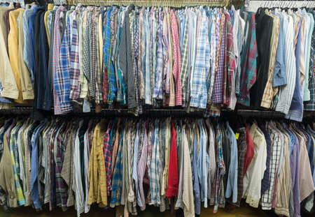 used clothes: Used shirts hanging at clothes rails of a thrift store