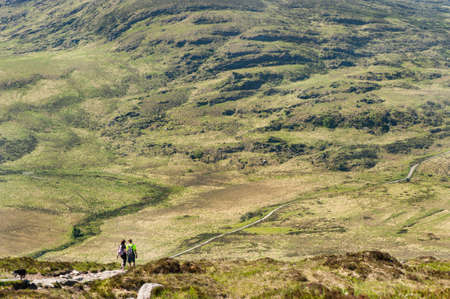 rugged: Couple hiking down the wild rugged landscape of Torc mountain in County Kerry, Ireland Stock Photo