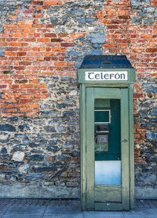 antique booth: Old vintage Irish telephone box and brick wall texture in rural Ireland Stock Photo