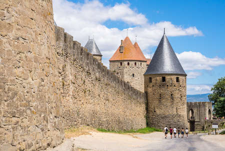 walled: Tourists walking towards an entrance of the walled castle fortress of Carcassonne in the south of France Editorial