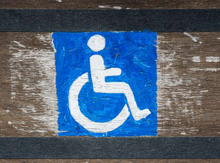 handicap sign: hand painted DIY handicap sign on grunge wood texture background Stock Photo