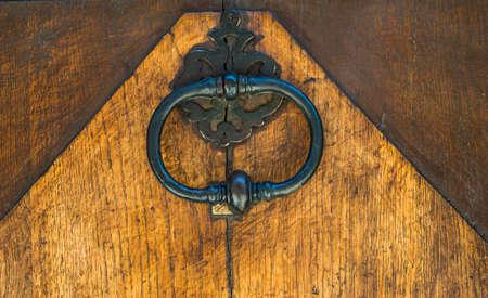 Vintage metal door knocker on sold wooden door background