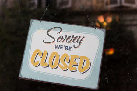 selling service: Vintage looking sorry were closed sign in a store window