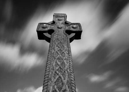 irish culture: Black and white Celtic cross gravestone with fast moving dramatic sky background Stock Photo