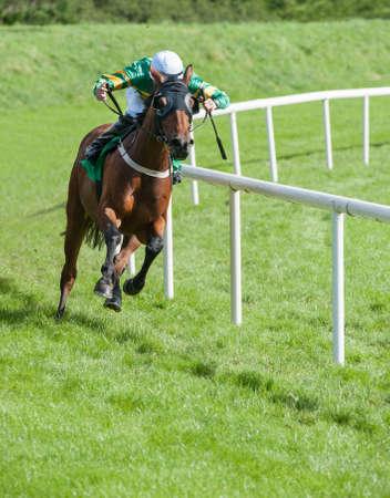 Jockey en paard galopperen rond de bocht van het circuit Stockfoto