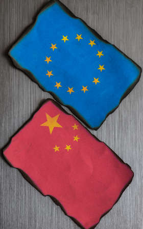 adversaries: Chinese and european flag side by side on brushed metal background
