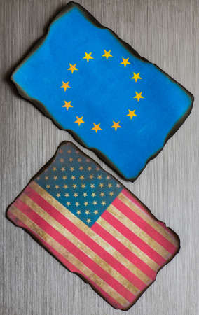 adversaries: American and European flag side by side on brushed metal grunge background