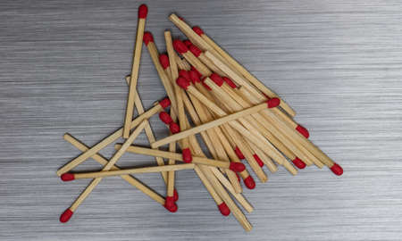Wooden Matchsticks spilled out on brushed metal background texture