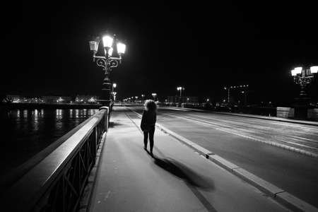 Woman walking on Pont de Pierre bridge, at Night, black & white, Bordeaux, France