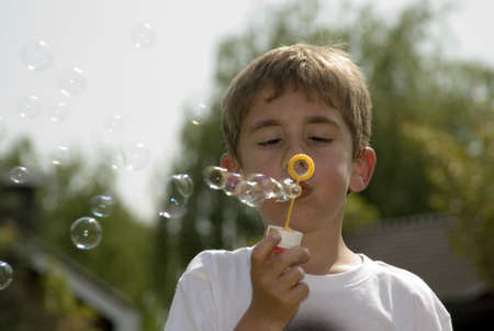 Young boy blowing soap bubbles Stock Photo - 1354632