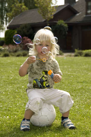 Young boy sitting on a football and blowing bubbles photo