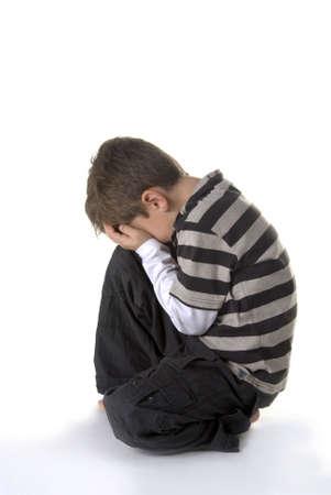ni�os tristes: un joven, sentado en el suelo, llorando  Foto de archivo