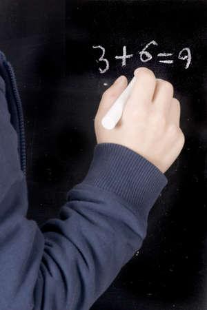 un muchacho está escribiendo una suma en la pizarra  Foto de archivo - 2434176