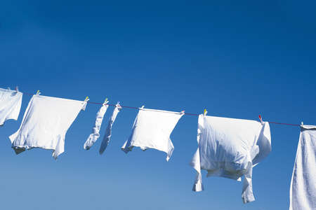 clothes line: White clothes hanging on the line against blue sky.