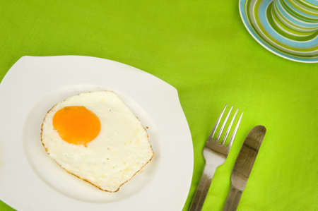 a fried egg on a plate with a fork and a knife