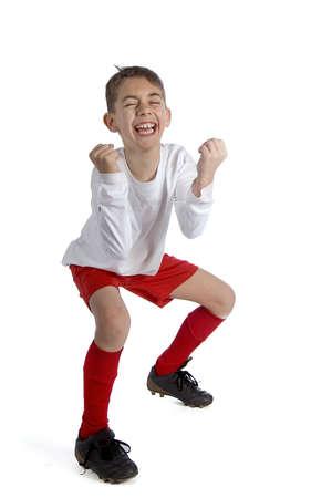 uniforme de futbol: un ni�o en uniforme de f�tbol celebrando un juego ganador!