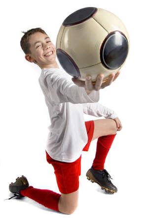uniforme de futbol: un ni�o en uniforme de f�tbol con un bal�n de f�tbol gigante Foto de archivo