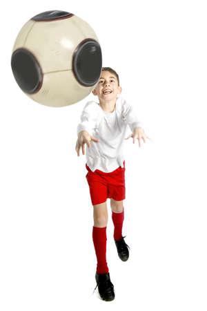 uniforme de futbol: un muchacho en el uniforme de f�tbol est� lanzando un bal�n de f�tbol