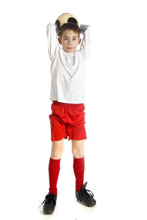 uniforme de futbol: un ni�o en uniforme de f�tbol sosteniendo un f�tbol a tirar Foto de archivo