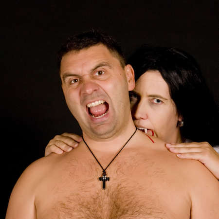 a vampire women bite a screaming man on black photo