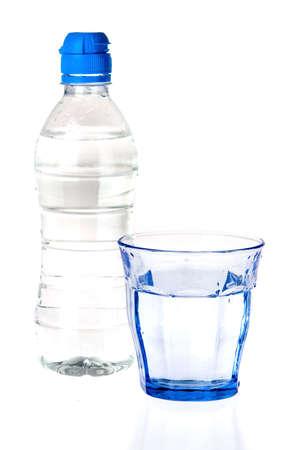 botella de plastico: un cristal azul y una botella de agua sobre un fondo blanco Foto de archivo