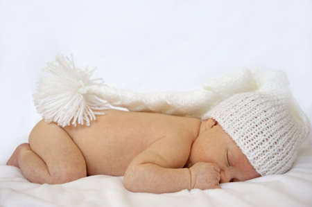 a sweet baby sleeping on a blanket with a knitted hat