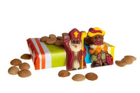 sint: Sweet candy -gingernuts- with a present and a chocolate sint and piet, c elebrating a dutch holiday called sinterklaas