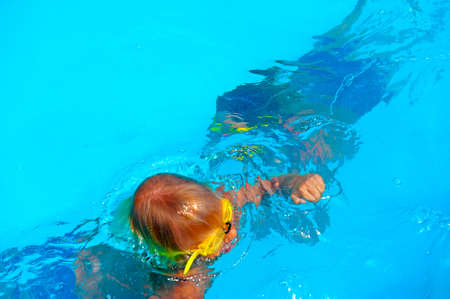 Two boys are swimming under water