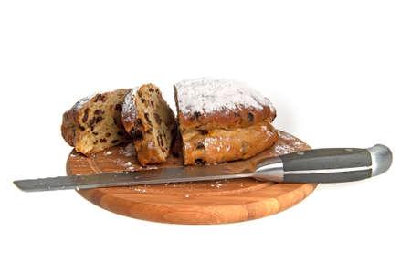 a raisin bread, cut in slices,  on a wooden cuttingboard
