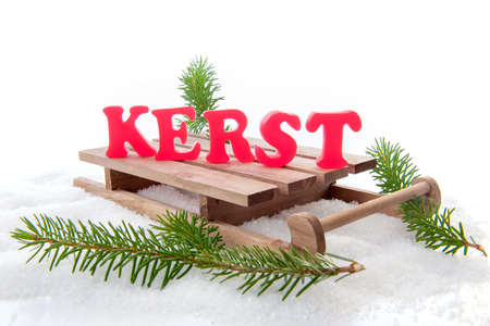 pine branch: The dutch word for christmas kerst, red letters on a sleigh, with a pine branch Stock Photo